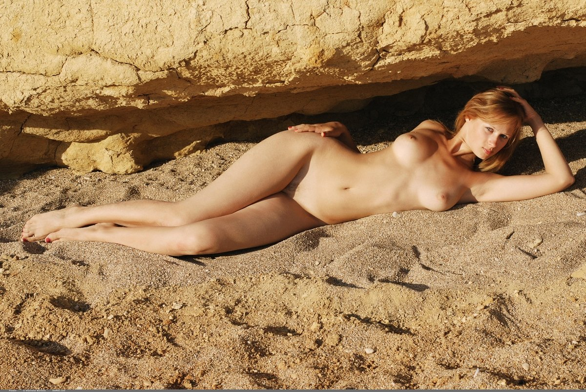 Рыженькая девушка голая сидит на песке