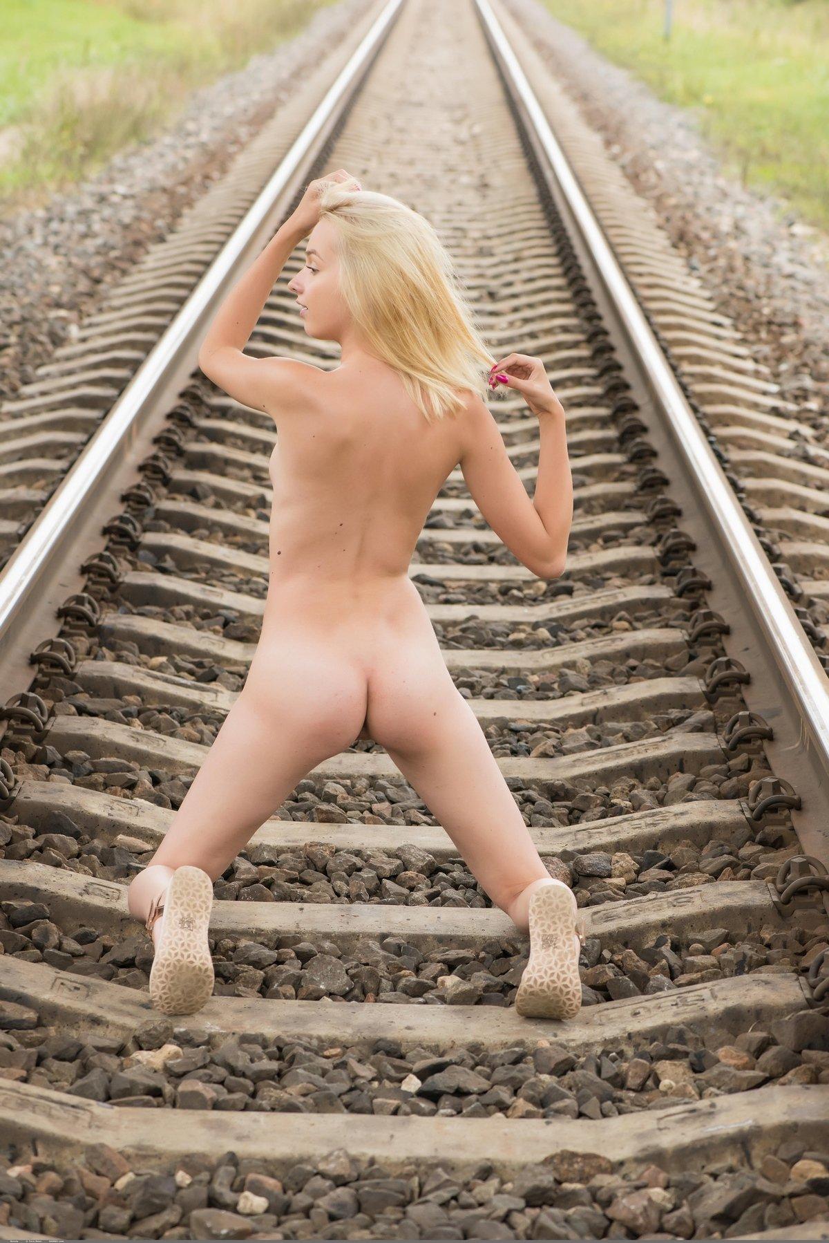 Ню голенькой блондинки на рельсах