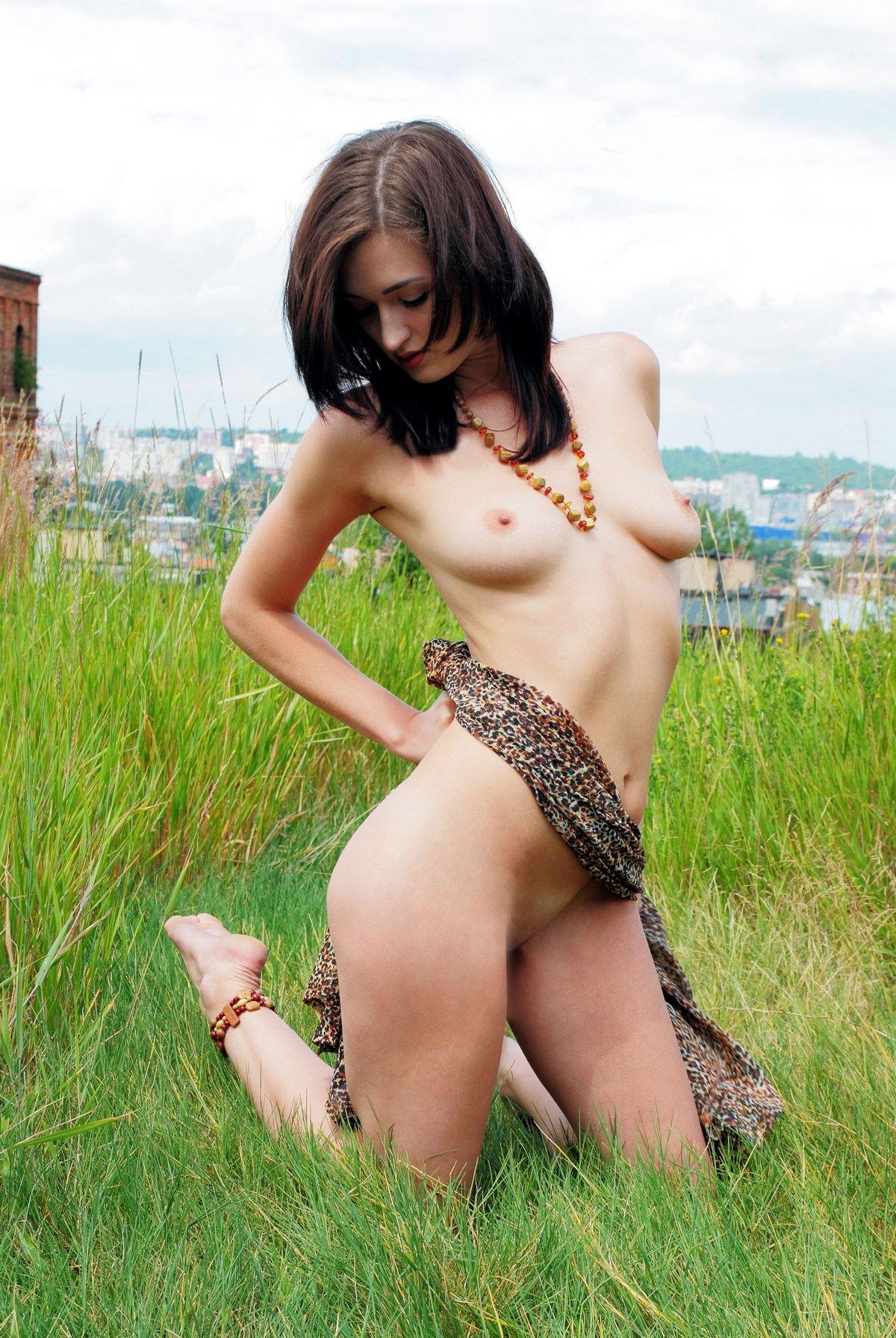 Брюнетка задирает платье и раздвигает ножки на полянке