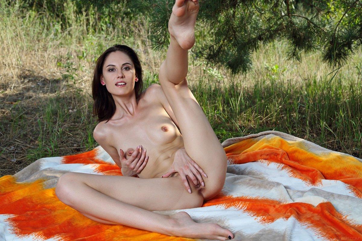 Худенькая барышня вставляет пальцы в пилотку на поляне секс фото