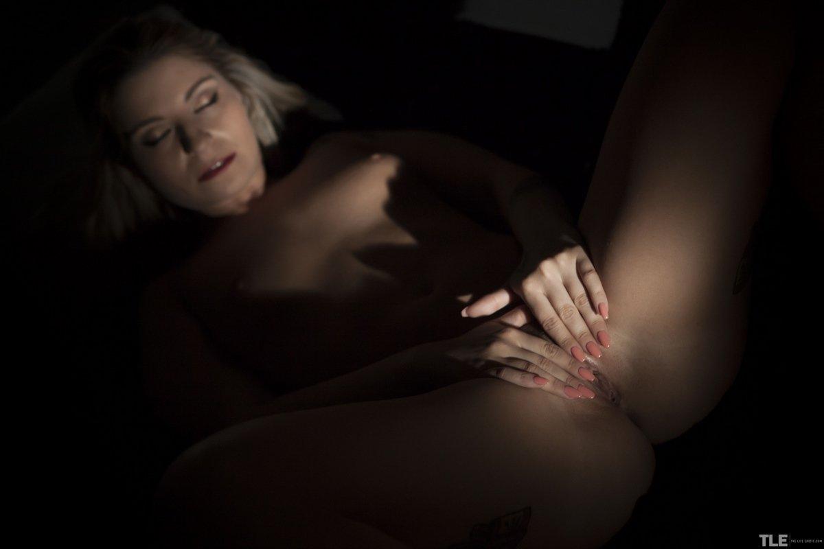 Светловолосая девушка блистает идеальное тело в темноте