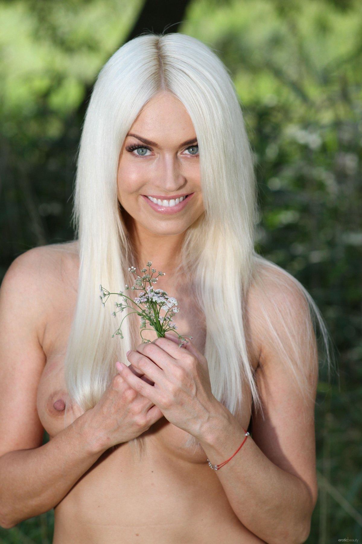 Симпатичная модель со свелыми волосами без нижнего белья в зеленых зарослях