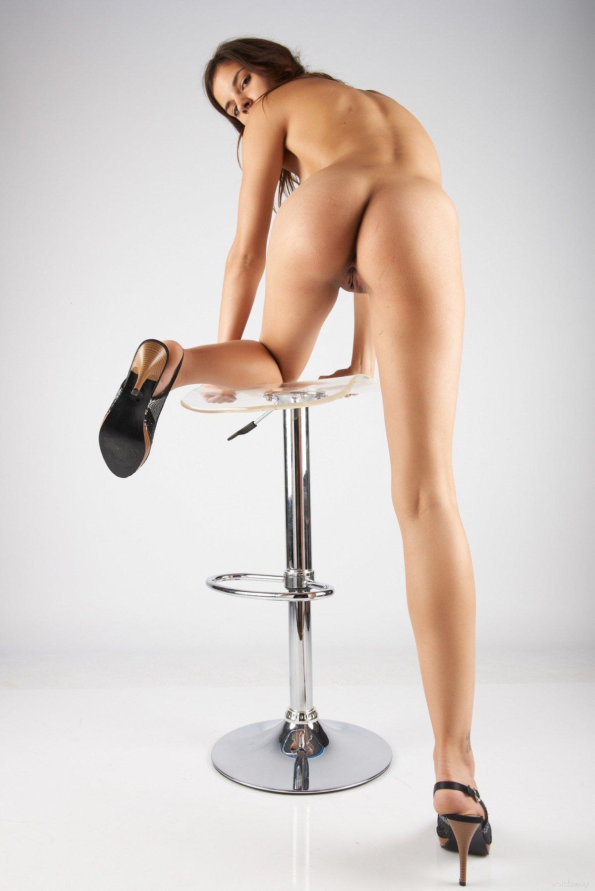Candice раздвигает загорелые ножки на высоком стуле