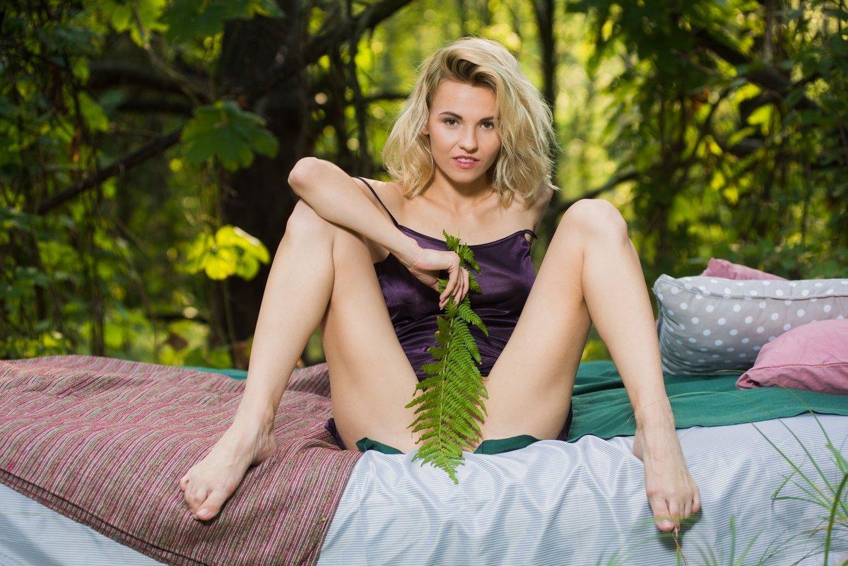 Голая красавица на кровати в лесу