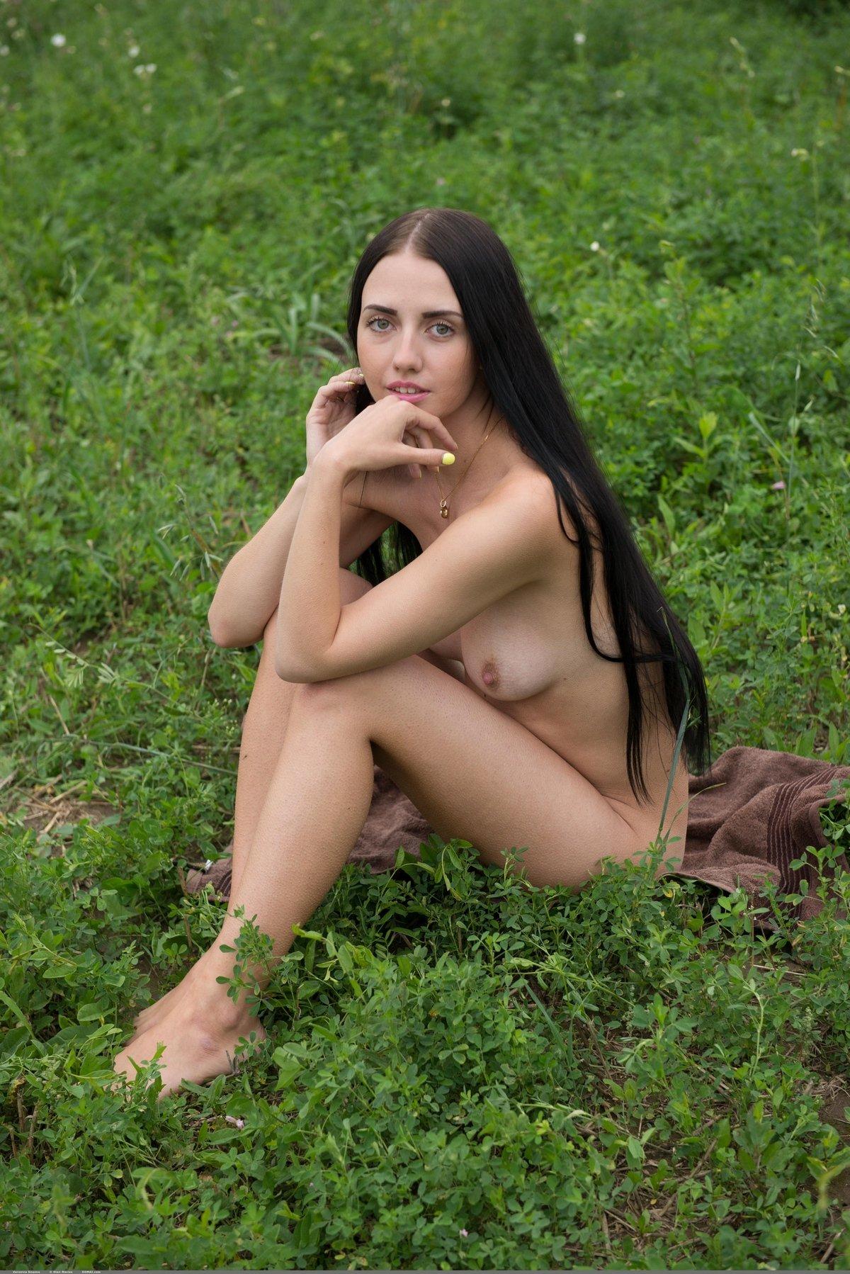 Брюнетка с длинными волосами на зеленой траве
