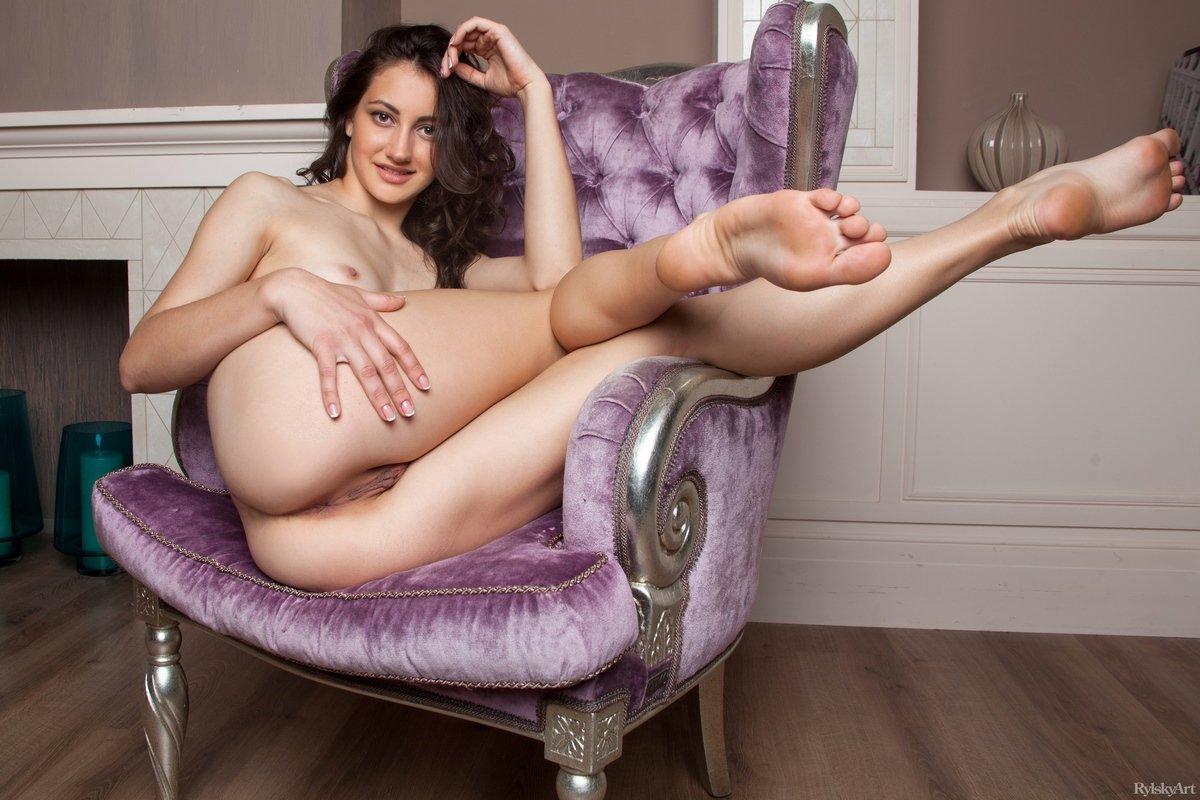 Черноволосая тёлка приподнимает ноги в кресле