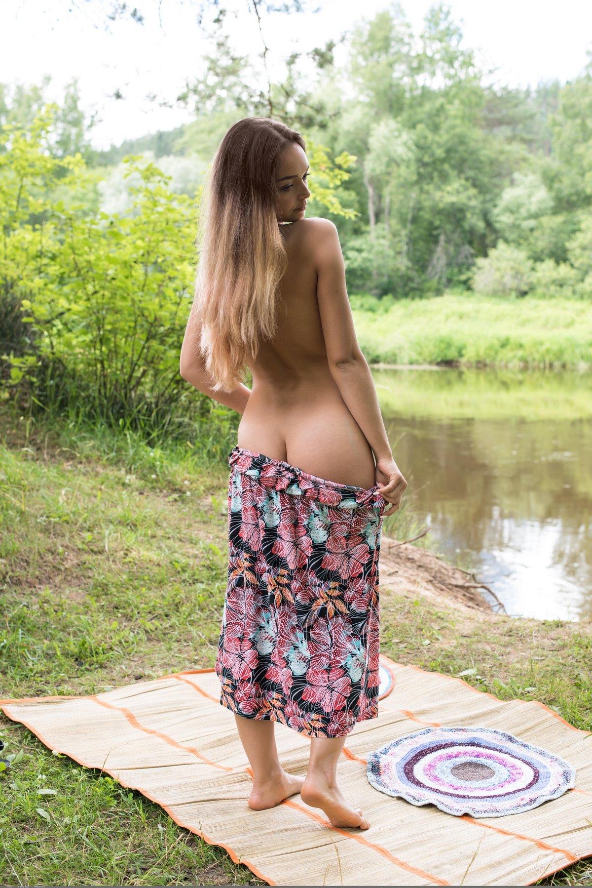 Загорелая мадам возле пруда без стрингов