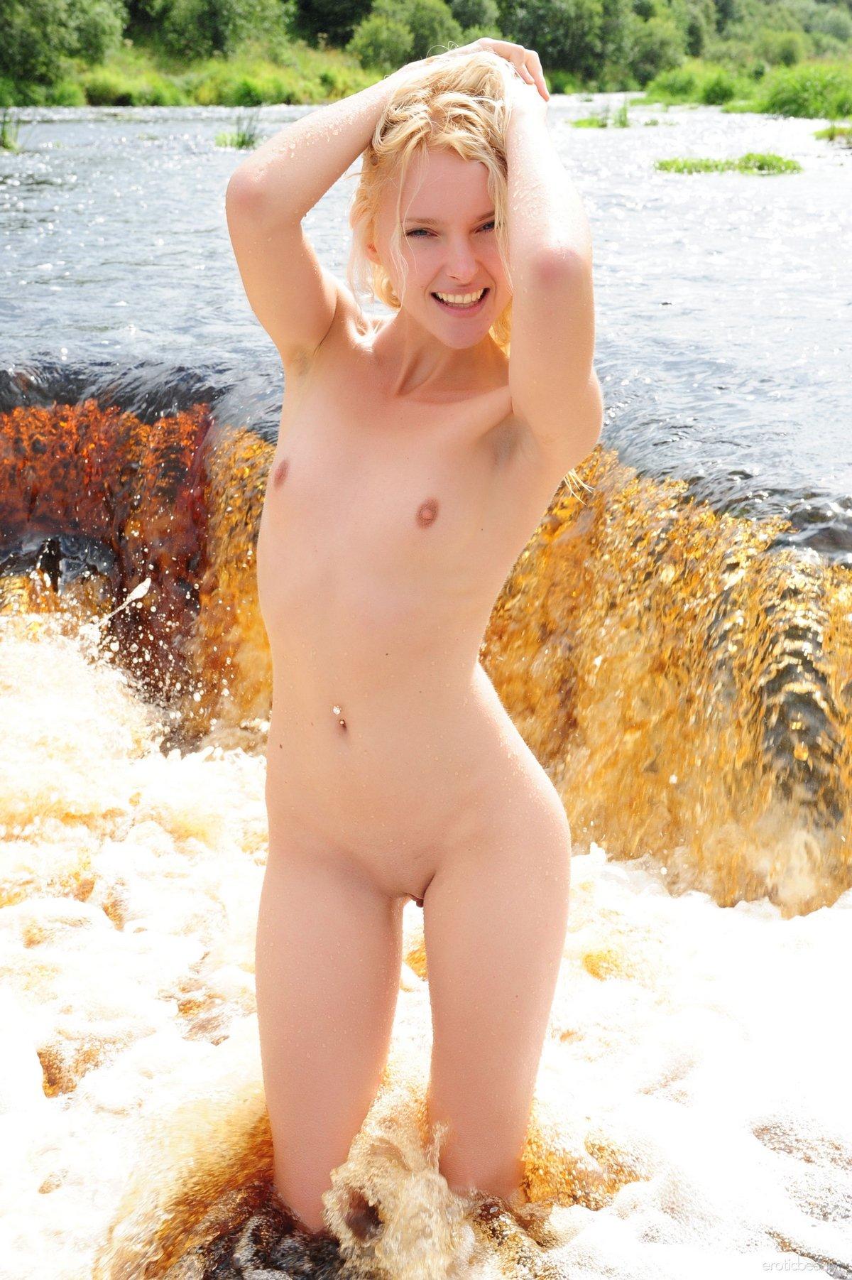 Обнаженная модель со свелыми волосами плавает в водопаде секс фото