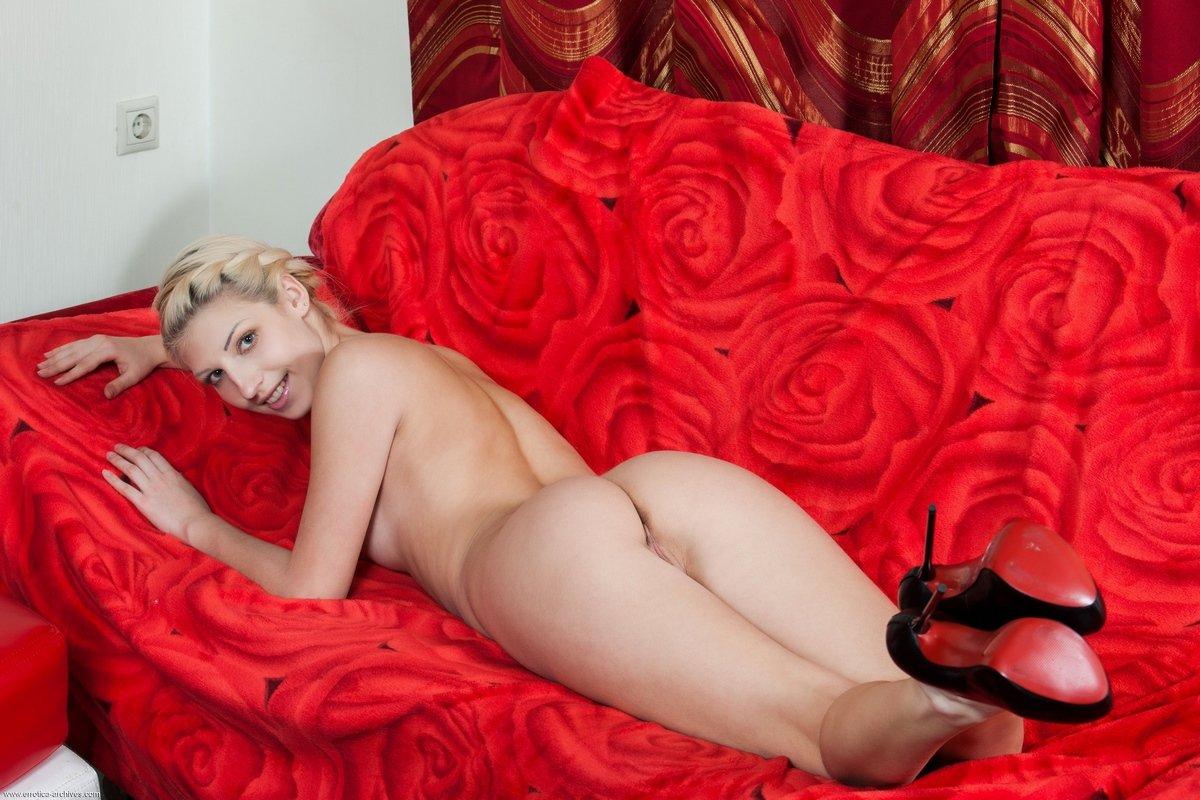 Светловолосая модель с маленькими сиськами сидит на красном диване
