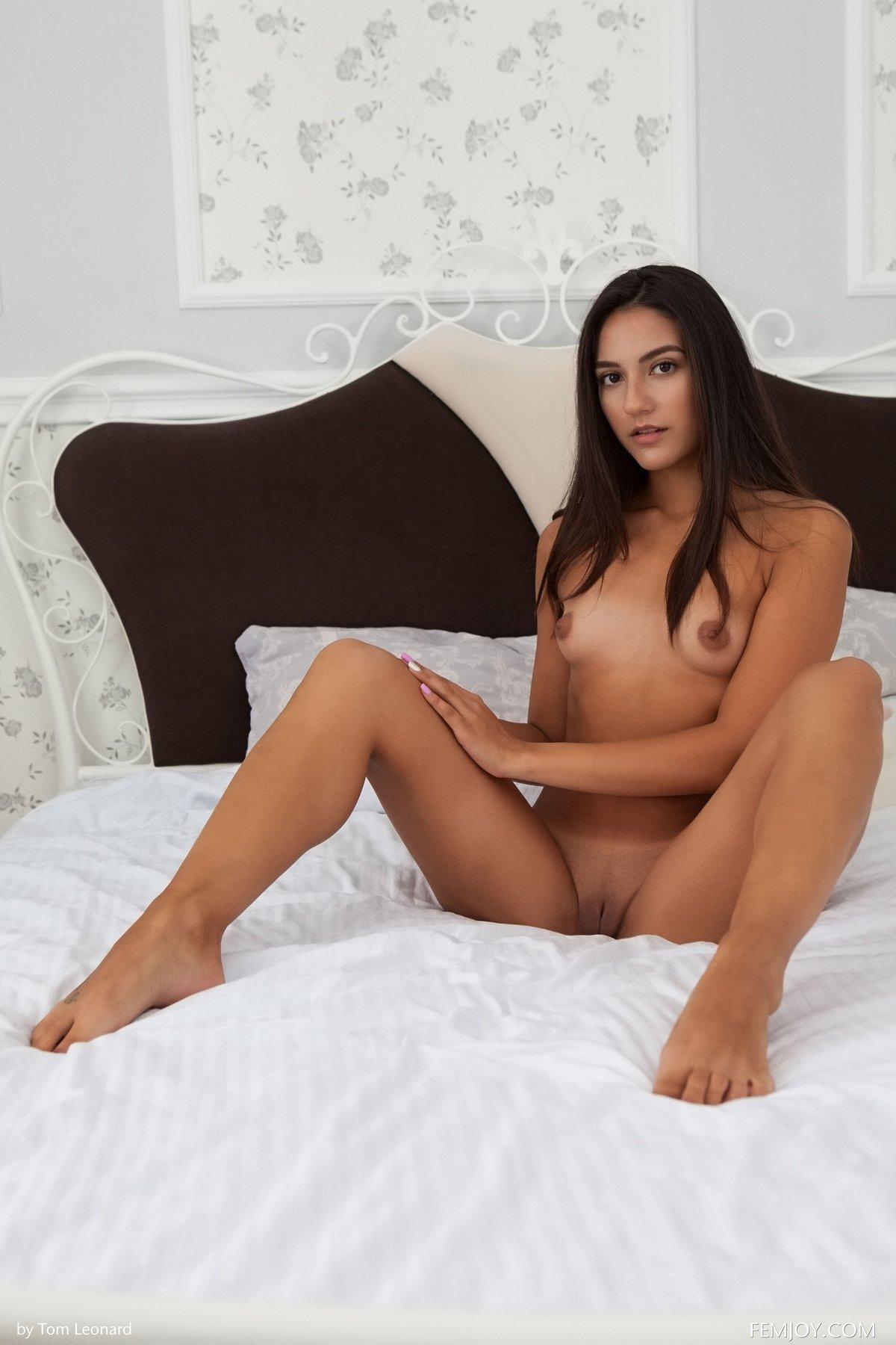 Молодая девушка с грудью нулевого размера сидит на кровати