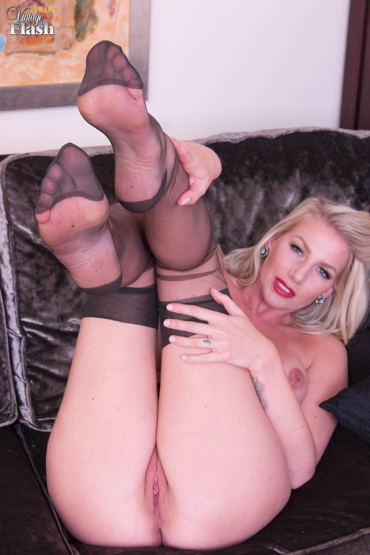 Женщина с силиконовой грудью раздвигает ноги в чулках