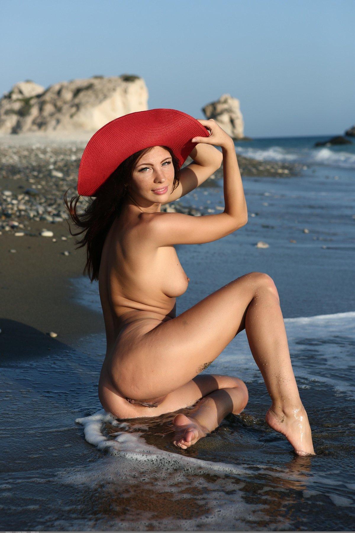 Голая красоточка в красной шляпе на пляже