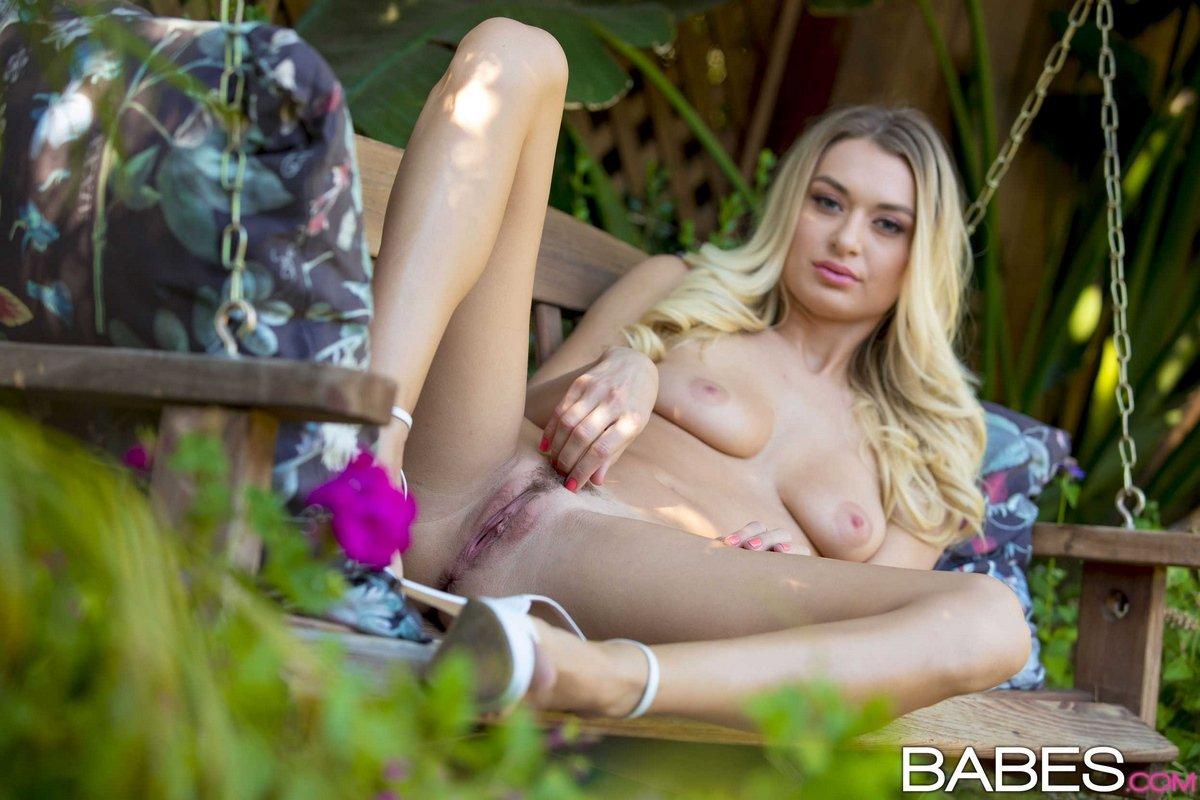 Красивая светловолосая девушка в саду раздевается