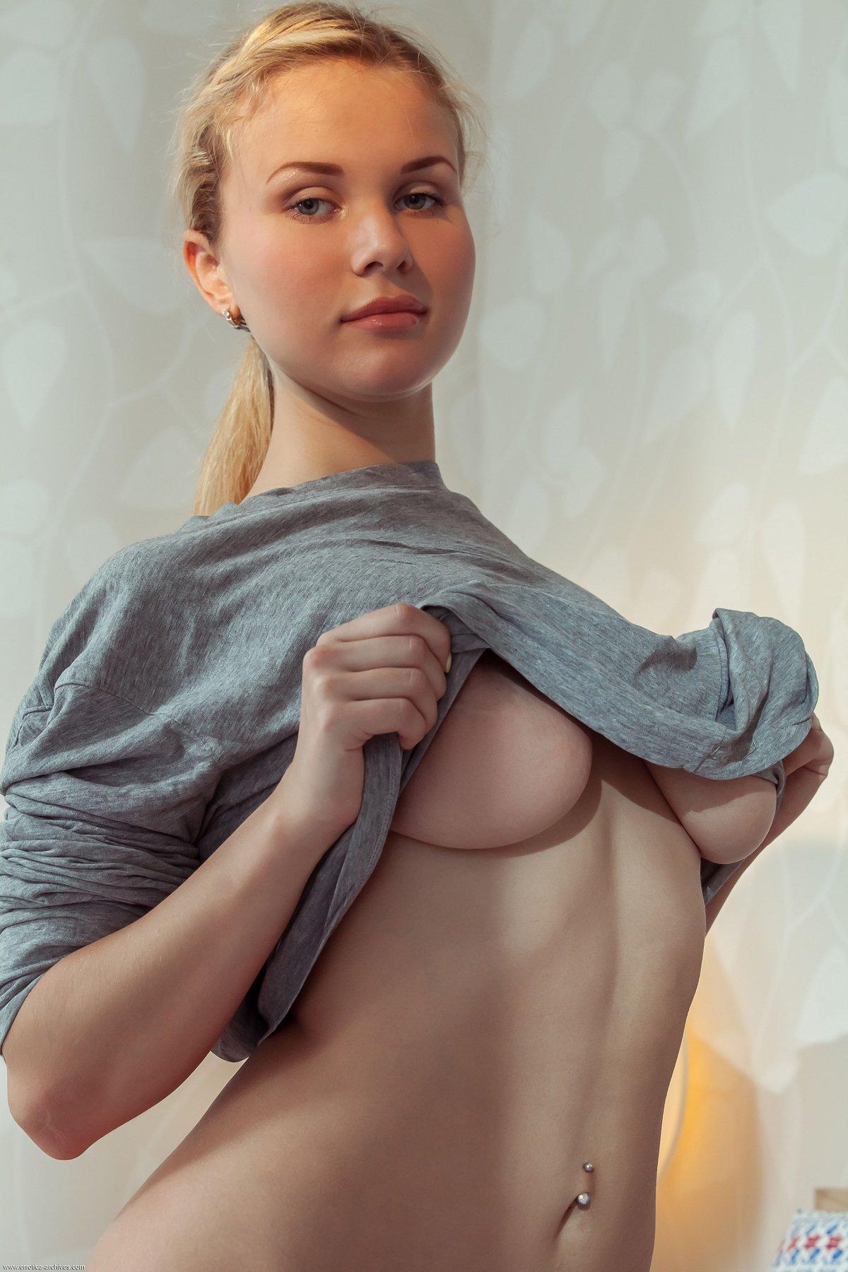 Красотка снимает футболку сидя на кровати