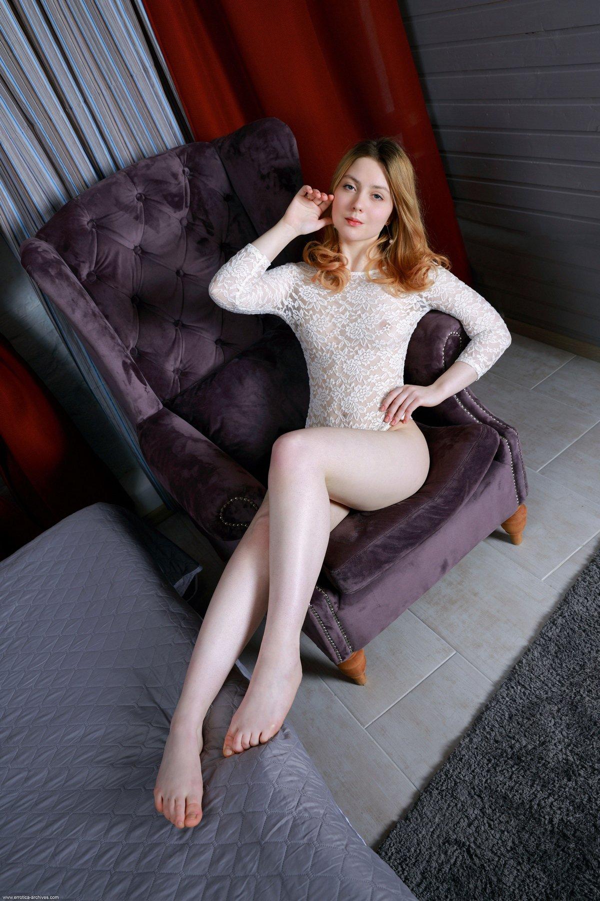 Рыжая девушка снимает кружевной наряд в мягком кресле