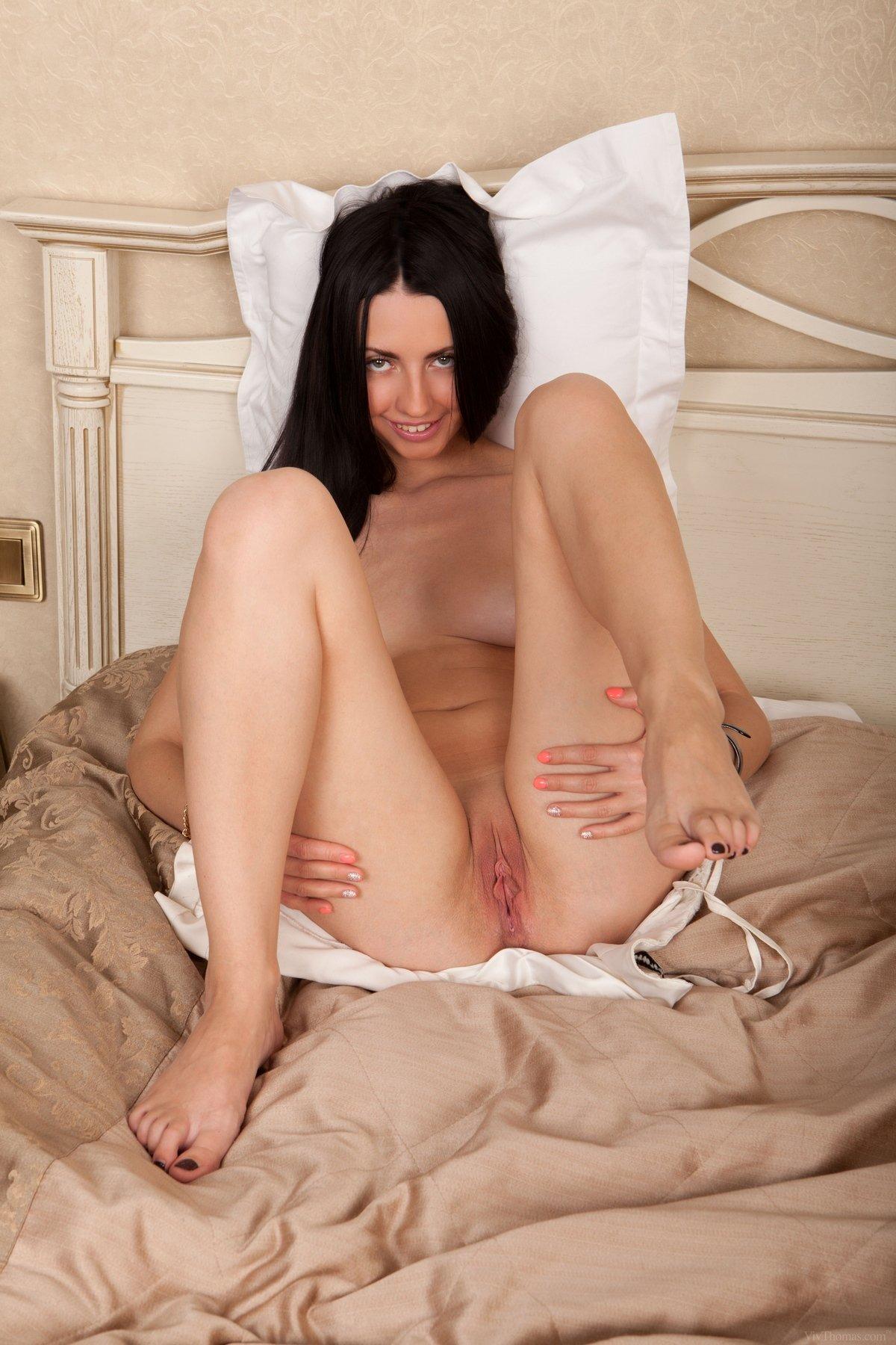 Шатенка в коротком платье валяется в спальне и оголяет письку