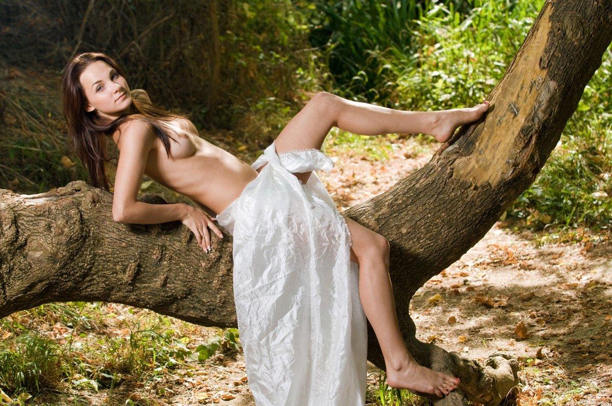 Девушка с белым шелковым покрывалом вокруг бедер возле лесного пруда