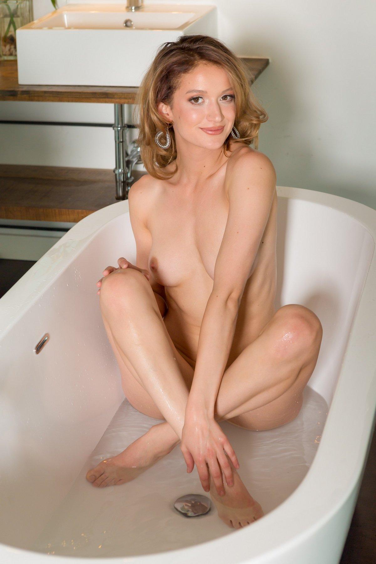 Блондиночка с чувственными губами на кроватке без нижнего белья