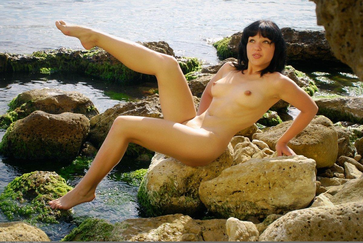 Обнаженная брюнетка купается в море