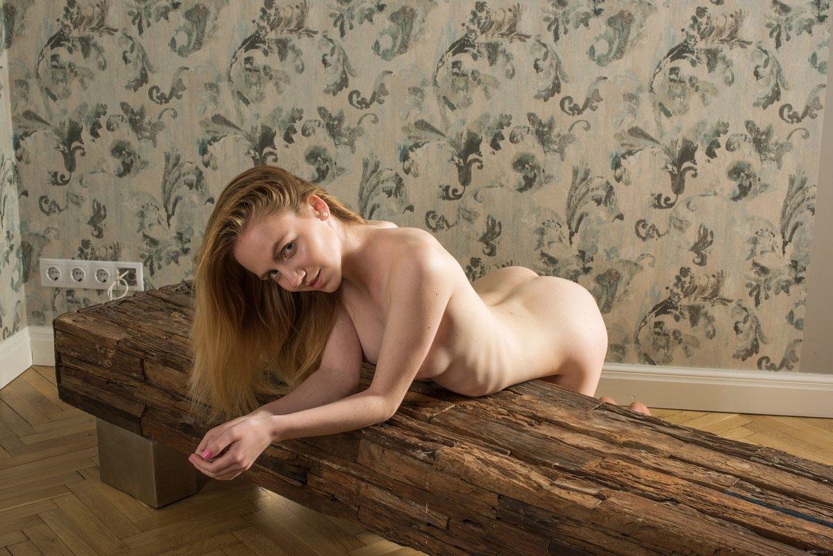 Молодая девушка с золотистыми волосами на деревянной скамье