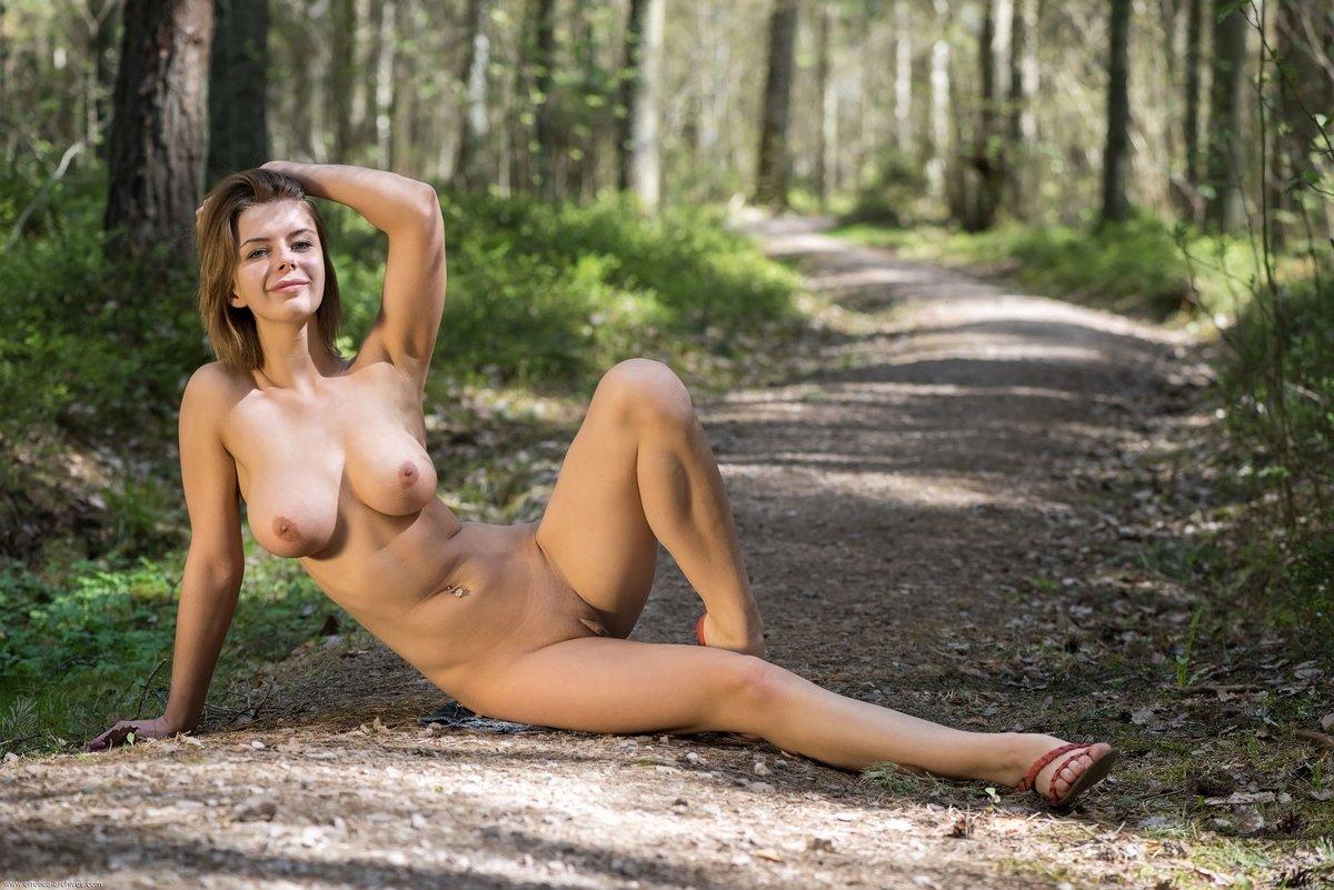 Светлая модель с нормальными сиськами ходит голая около дерева