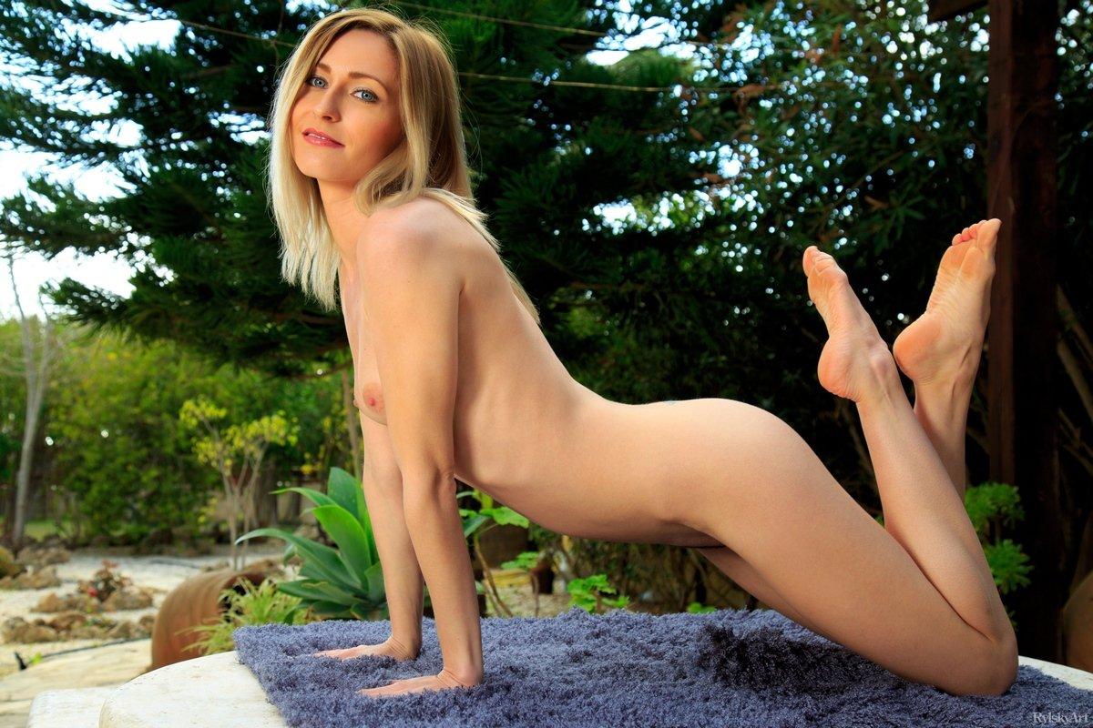 Обнаженная блондинка показывает стройное тело на природе