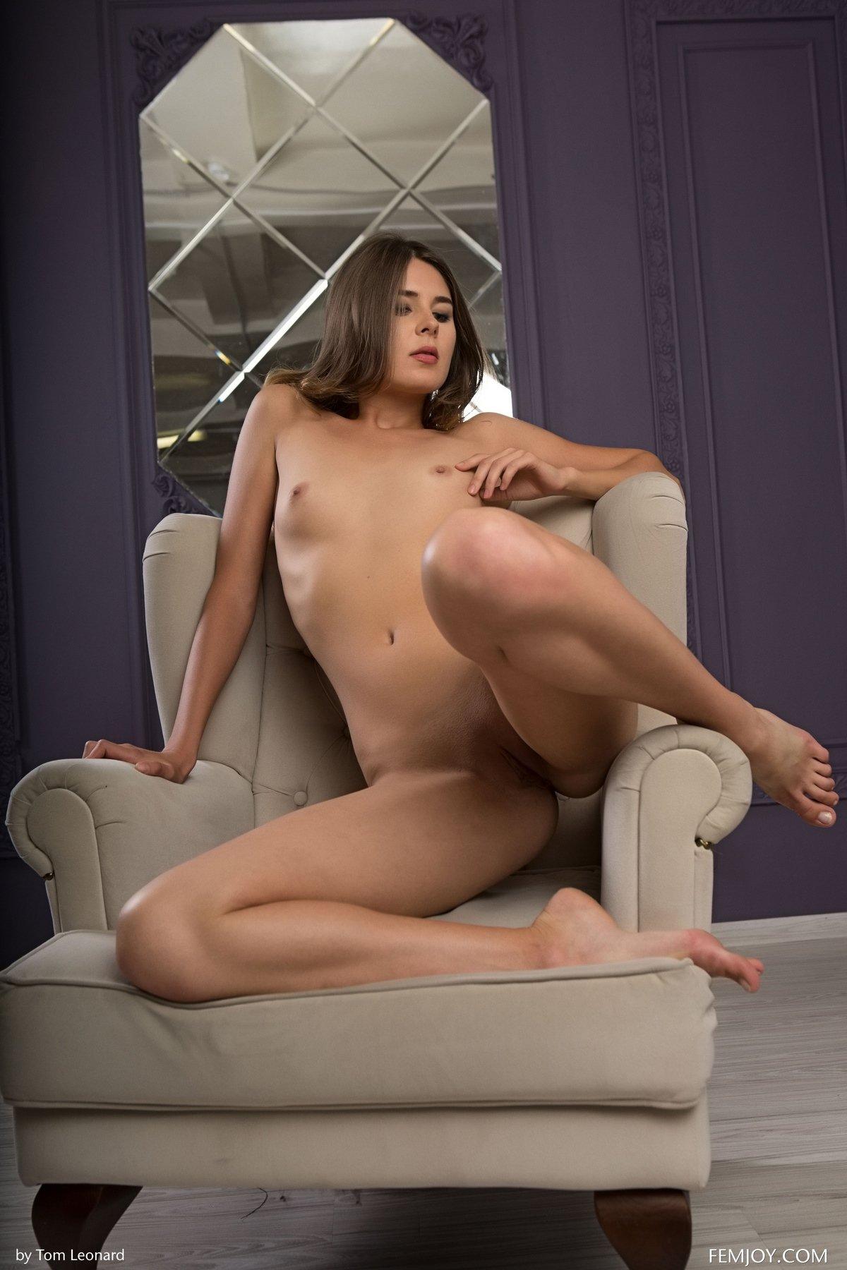 Красивая девушка сняла черное платье и показывает длинные ножки в кресле