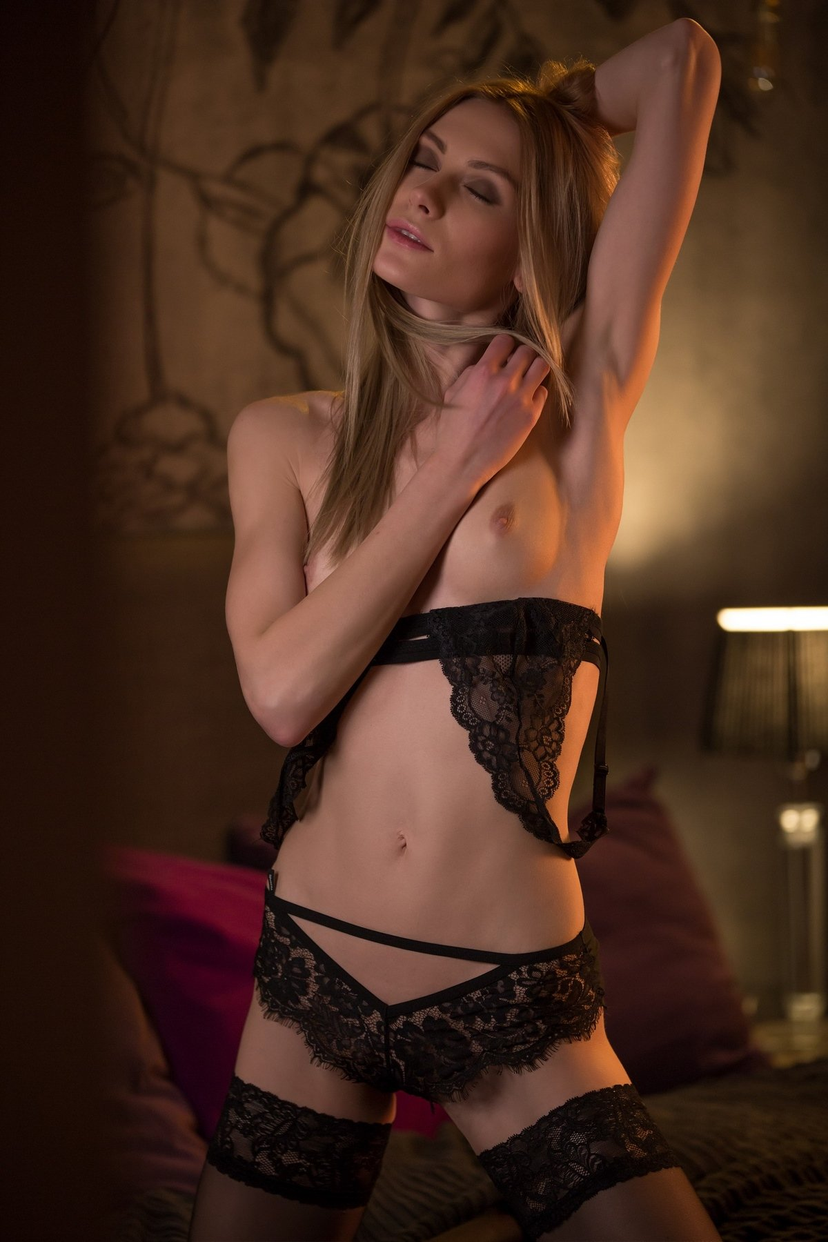 Блондинка сексуально позирует на кровати в черном корсете и в черных кружевных чулках